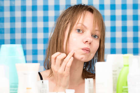 frontal portrait: Girl is applying cosmetic product on her problem skin areas in bathroom. Skincare and beauty concept. Frontal portrait