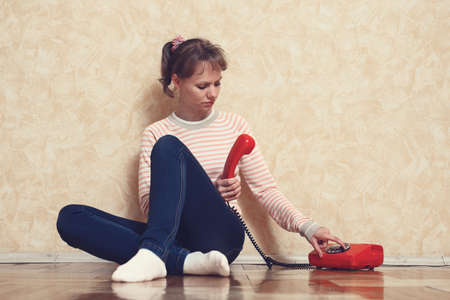 expects: Sad young white-skinned girl is sitting on parquet floor beside the wall and calling by red phone Stock Photo