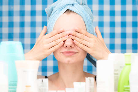 shower stall: Young white-skinned girl with towel on head has covered her eyes by hands in bathroom. Skincare and beauty concept. Frontal portrait