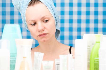frontal portrait: Girl with towel on her head is looking at cosmetic products in bathroom. Skincare and beauty concept. Frontal portrait