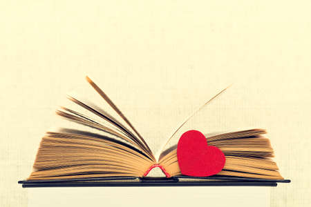 yellow pages: The opened book with the turned yellow pages and heart on a light background from weaving