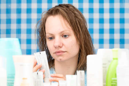 frontal portrait: Girl is reading inscription on cosmetic product in bathroom. Skincare and beauty concept. Frontal portrait