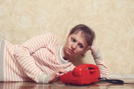 expects: Sad young white-skinned girl is sitting on parquet floor beside the wall near to red phone