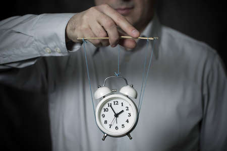 govern: Business man manages a clock, hanging on cords and symbolizing the time, on dark background