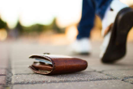 inattention: Girl had lost leather wallet with money on the street. Close-up of wallet lying on the sidewalk and feet of outgoing girl