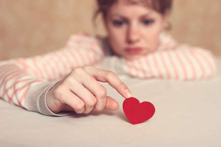 amorousness: Sad girl is holding heart symbol by her finger and looking at it. Love and relationships concept Stock Photo
