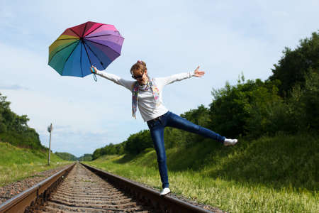 hand rails: Young white-skinned girl is walking on the rails with colorful umbrella in her hand in sunny summer day Stock Photo