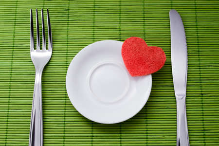 Symbol of heart lie on a small saucer and denote sympathy to diet