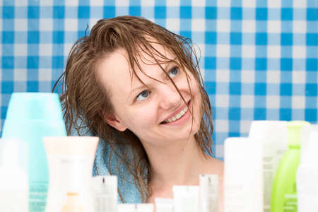 shower stall: Girl is drying her hairs surrounded by various cosmetics in bathroom. Skincare and beauty concept. Frontal portrait