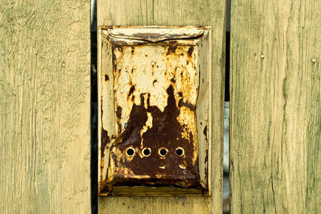 addressee: Old rusty mailbox is hanging on old wooden fence with cracks