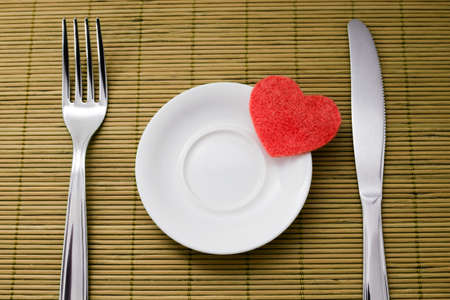 dinnertime: Symbol of heart lie on a small saucer and denote sympathy to diet