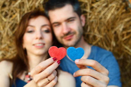 liaison: Couple of lovers is holding in their hands red and blue hearts and looking at them on hay background