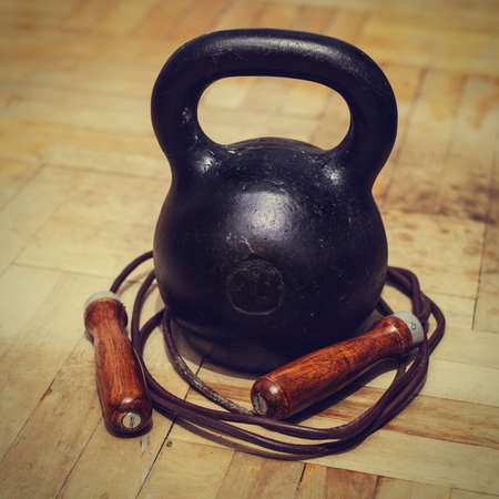 tinted: Black cast iron kettlebell and leather jumping rope at old parquet floor of room. Healthy lifestyle and physical activity concept. Tinted image