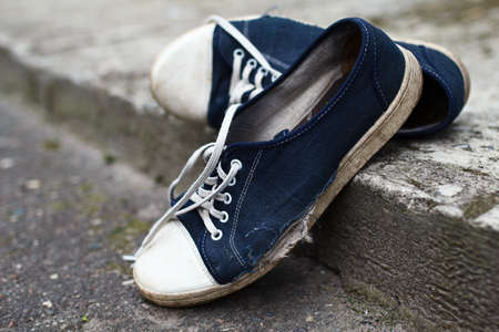 destitution: Shabby textile holey blue gumshoes with white laces had abandoned at the street in summer Stock Photo
