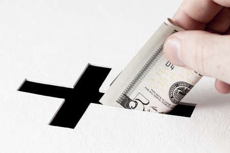 deeds: Hand of parishioner is inserting five dollars into hole for donations in form of Christian cross on white background. Idea of donations for church and good deeds