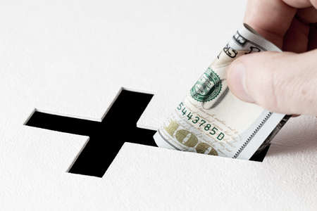 deeds: Hand of parishioner is inserting one hundred dollars into hole for donations in form of Christian cross on white background. Idea of donations for church and good deeds