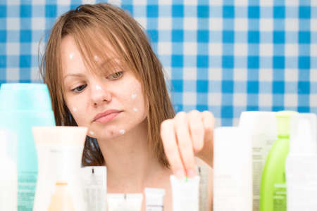 shower stall: Girl is choosing a cosmetic product among set of cosmetics in bathroom. Skin care and beauty concept. Frontal portrait