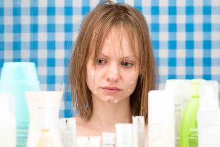 frontal portrait: Young white-skinned girl with problem skin is weeping in bathroom in front of cosmetic products on blue-white curtains background  Skincare and beauty concept. Frontal portrait