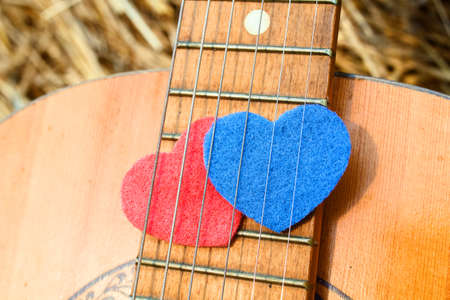 combining: Two heart symbol, red and blue, together under the strings of the guitar. The concept of combining romance and musical creativity