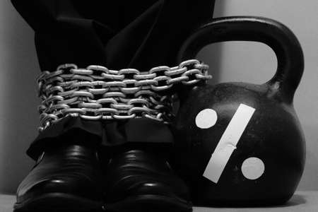 drawn metal: Businessman legs dressed in black trousers and shoes is fastening by metal chain to black iron kettlebell with drawn percent sign. Concept of percent payments. Monochrome image Stock Photo