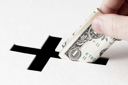 deeds: Hand of parishioner is inserting one dollar into hole for donations in form of Christian cross on white background. Idea of donations for church and good deeds Stock Photo