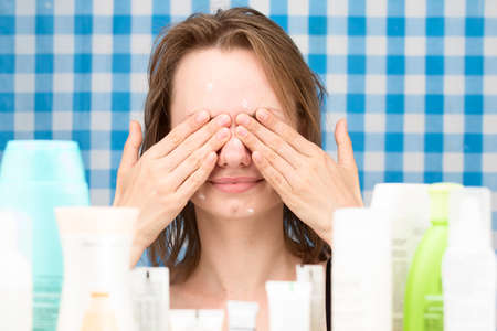 Young girl with problem skin is closed her eyes in front of set of cosmetics in bathroom. Skin care and beauty concept. Frontal portrait Stock Photo