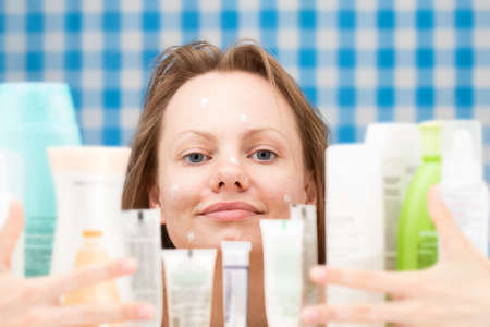 contented: Contented girl is embracing various cosmetics in bathroom