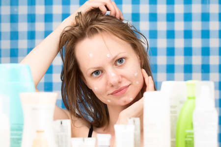 shower stall: Young girl with wet hairs is posing in the bathroom in front of cosmetic products at blue-and-white checkered curtains background. Skincare and beauty concept. Frontal portrait Stock Photo