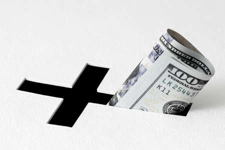 white backing: One hundred dollars have been insert into hole for donations in form of Christian cross on white background. Idea of donations for church and good deeds