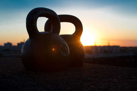 adroitness: Pair of black one-pood kettlebells at sunset background over the city. Concept of access for health improvement and physical development in free time after busy day