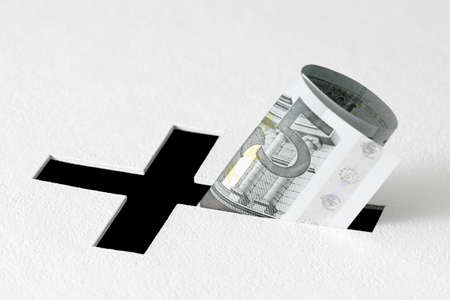 white backing: Five euros have been insert into hole for donations in form of Christian cross on white background. Idea of donations for church and good deeds