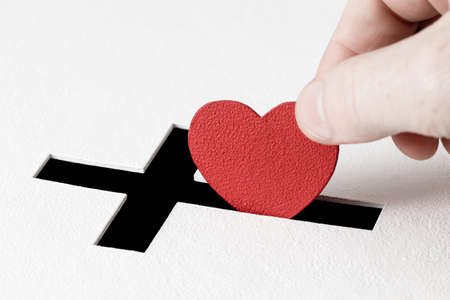 white backing: Hand of parishioner is inserting heart symbol into hole for donations in form of Christian cross on white background. Idea of sincere devotion for faith with all heart Stock Photo