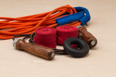 implements: Sports equipment for boxing. Boxing bandages,  expander, multiple fiber and leather jump rope on light background