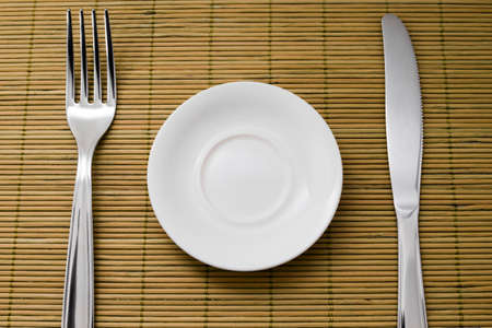 small plate: Small plate for diet next to a knife and fork on green bamboo placemats