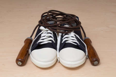 calisthenics: New keds with white laces and a leather skipping rope with wooden handles on a light wooden background