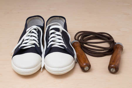 leathern: New keds with white laces and a leather skipping rope with wooden handles on a light wooden background