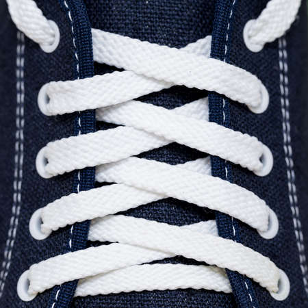 lacing sneakers: Lacing with white laces at the blue cloth sports Shoe with stitches of white thread