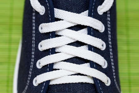 lacing sneakers: Lacing with white laces at the blue cloth sports Shoe with stitches of white thread. All on a bright green background from bamboo sticks
