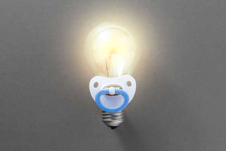 zeal: Burning light bulb with pacifier on a gray background. Idea for a startup in the beginning of its development. Concept of a startup