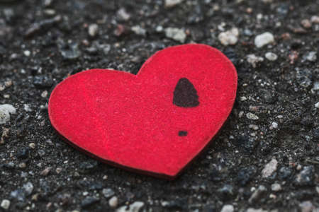 liaison: Lonely mans heart with a womens footprint lying on asphalt. Concept of breakup long relations Stock Photo