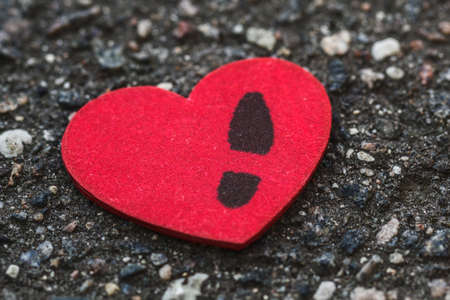 Lonely womens heart with a mans footprint lying on asphalt. Concept of breakup long relations