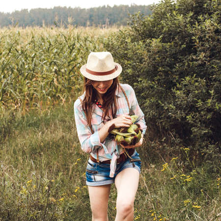 Young girl dressed in shorts and with summer hat is going with maize in her hands and smiling