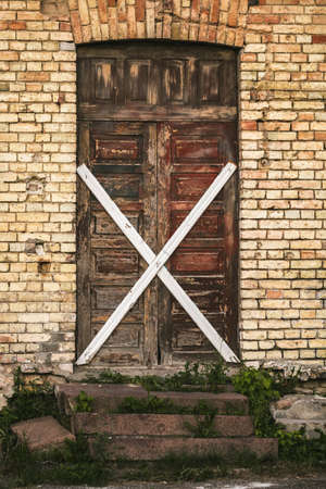 boarded: Old wooden door in a brick building boarded up crosswise Stock Photo