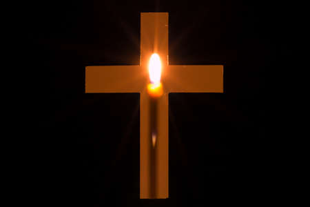 blazes: Candle is glowing behind a hole in shape of Christian cross. Concept of Christianity