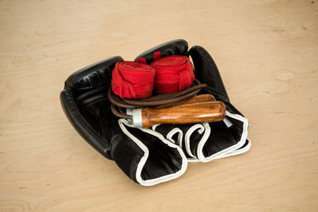 fervour: Black Boxing gloves, red bandages and leather jump rope on a light background made of plywood