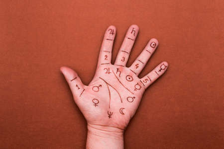 Palm of left hand with drawn symbols of palmistry. Concept of chiromancy Stock Photo