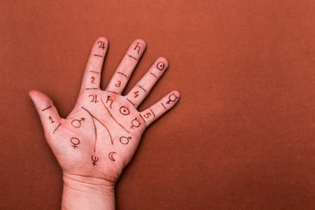omens: Palm of left hand with drawn symbols of palmistry. Concept of chiromancy Stock Photo