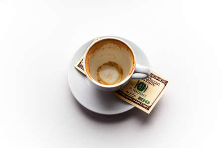 Empty Cup on the saucer and a hundred dollar bill on white background