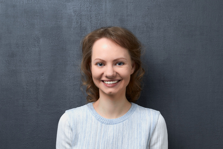 Studio close-up portrait of cute happy caucasian girl with fair hair, smiling broadly with teeth and looking at camera, standing against gray background, happiness concept