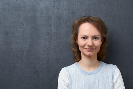 Studio close-up portrait of cute happy caucasian girl with fair hair, smiling broadly and looking at camera, standing against gray background, happiness concept